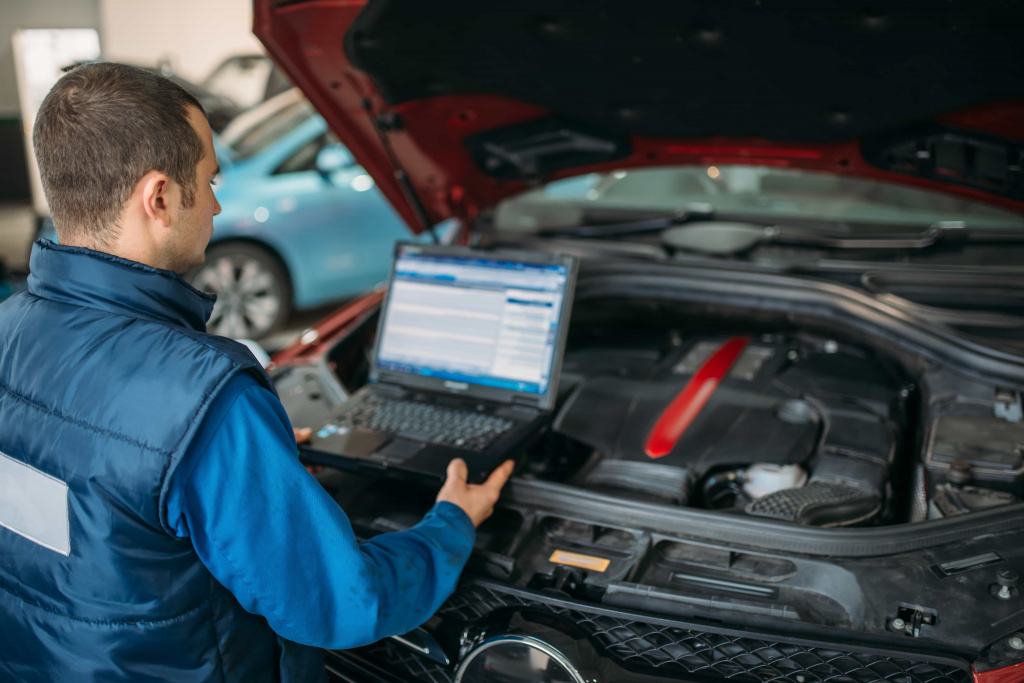 engineer-makes-computer-diagnostics-of-car-engine.jpg